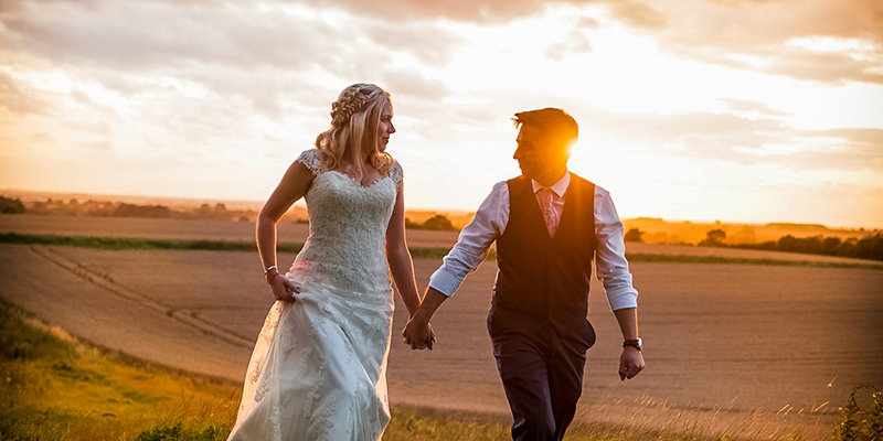 romantic wedding couple holding hands at sunset
